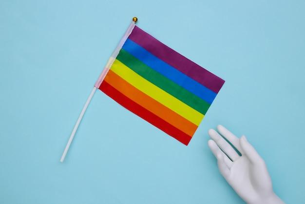 Mão de manequim e a bandeira do arco-íris lgbt sobre fundo azul. parada gay, liberdade, tolerância