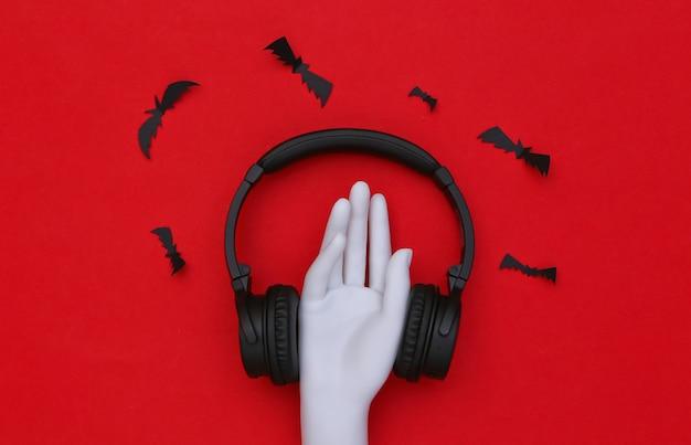 Mão de manequim e fones de ouvido estéreo com morcegos em fundo vermelho