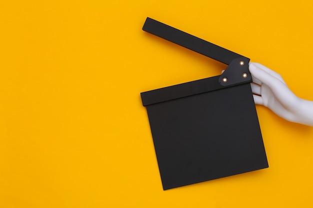 Mão de manequim segurando claquete de filme em fundo amarelo