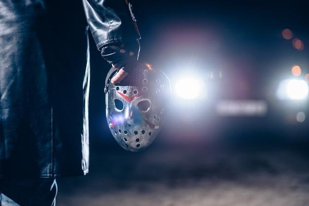 Mão de maníaco serial com closeup de máscara de hóquei sangrenta, luz do carro à noite. horror, assassino sangrento
