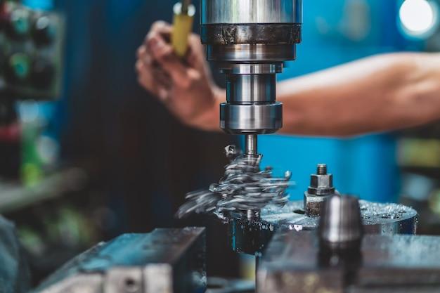 Mão de maquinista profissional trabalhando com fresadora em fábrica de metalurgia