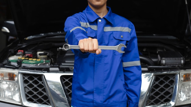 Mão de mecânico de automóveis com chave oficina de conserto de automóveis