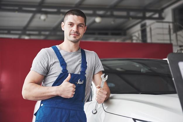 Mão de mecânico de automóveis com uma chave inglesa. oficina de reparação automóvel.