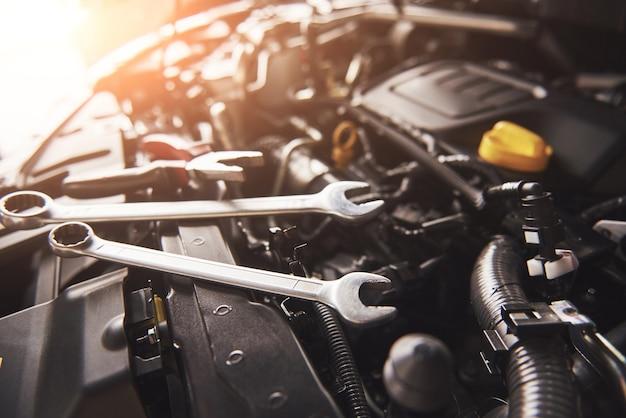 Mão de mecânico verificando e consertando um carro quebrado na garagem de serviço.