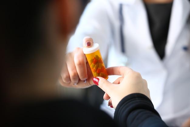 Mão de médico de medicina feminina segurar o frasco de comprimidos
