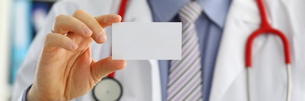 Mão de médico de medicina masculina segurando o cartão em branco.