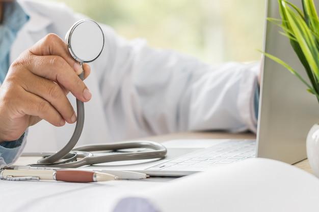 Mão de médico de medicina segurando estetoscópios na sala de consultoria, trabalhando no computador portátil na mesa na clínica