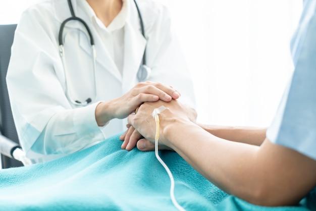 Mão de médico feminino reconfortante em seu paciente sênior