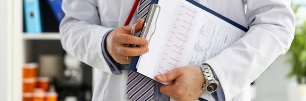 Mão de médico masculino segurar caneta prata preenchendo lista de histórico do paciente na área de transferência. examinador físico doença prevenção custódia visita rodada cheque 911 prescrever remédio conceito de estilo de vida saudável