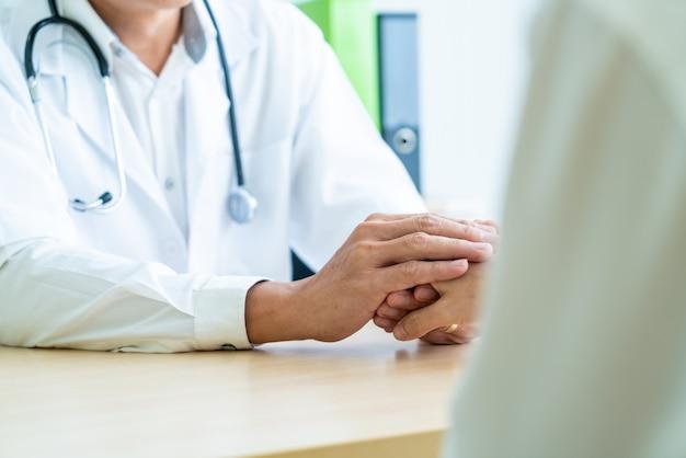 Mão de médico reconfortante seu paciente do sexo feminino