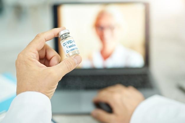 Mão de médico segurando frasco de vacina contra coronavírus