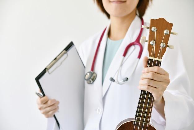 Mão de médico segurando o ukulele (instrumento musical), musicoterapia