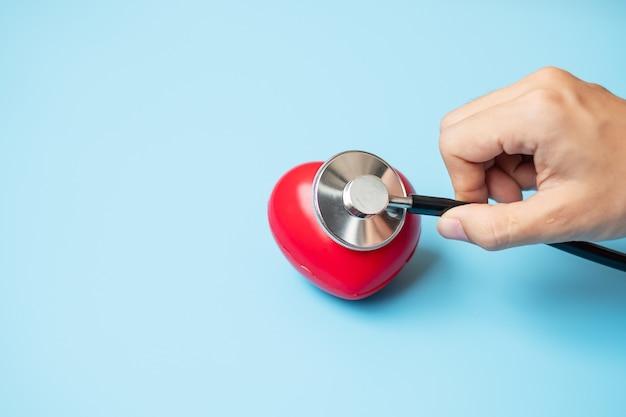 Mão de médico segurando um estetoscópio com coração vermelho