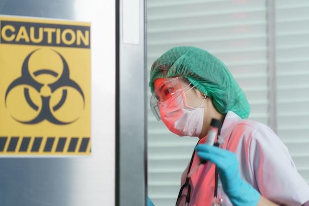 Mão de médico segurando um tubo de ensaio de amostras de sangue dentro no sinal de risco biológico no congelador