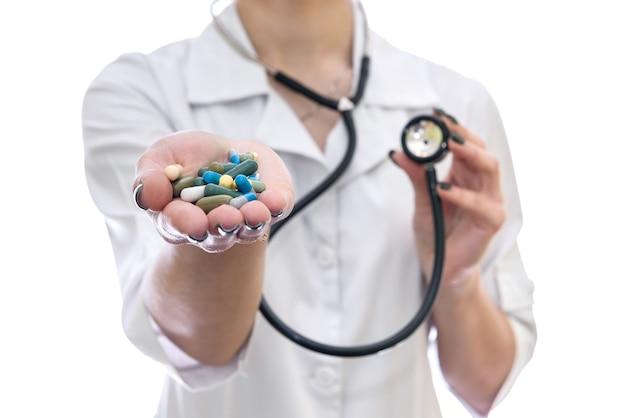Mão de médicos com comprimidos e estetoscópio isolado