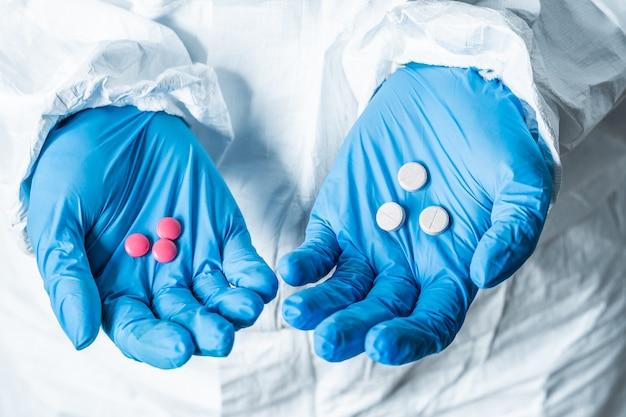 Mão de médicos segurando muitas pílulas diferentes