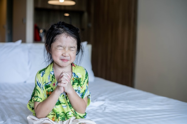 Mão de menina asiática orando, mãos postas em conceito de oração pela fé, espiritualidade e religião.
