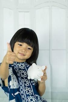 Mão de menina asiática segurando o cofrinho branco, aprenda a economizar para o conceito de futuro.