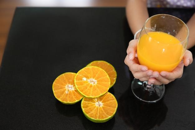 Mão de menina com copo de suco de laranja na cozinha
