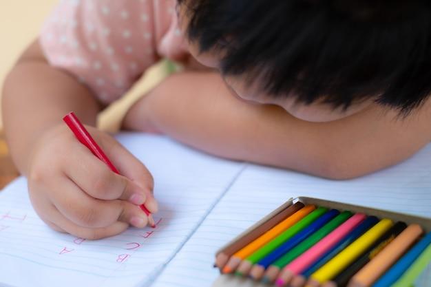 Mão de menina com lápis escrevendo palavras em inglês no papel branco do bloco de notas