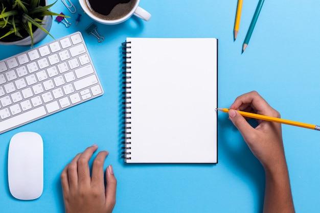 Mão de menina, desenho de papel em branco, mesa de escritório top view com computador e material de escritório