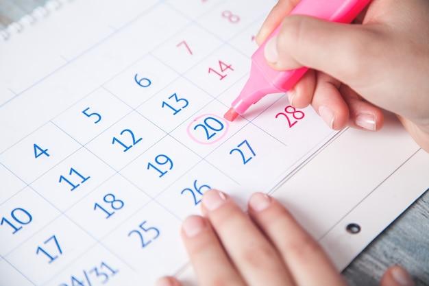 Mão de menina marca o calendário com um marcador.