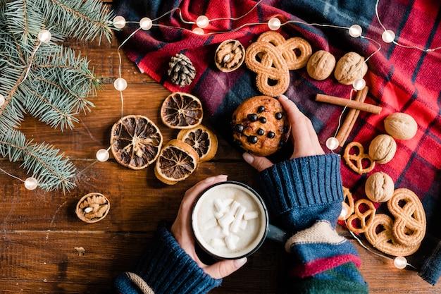 Mão de menina pegando bolinho caseiro e tomando uma bebida quente com marshmallows na véspera de natal