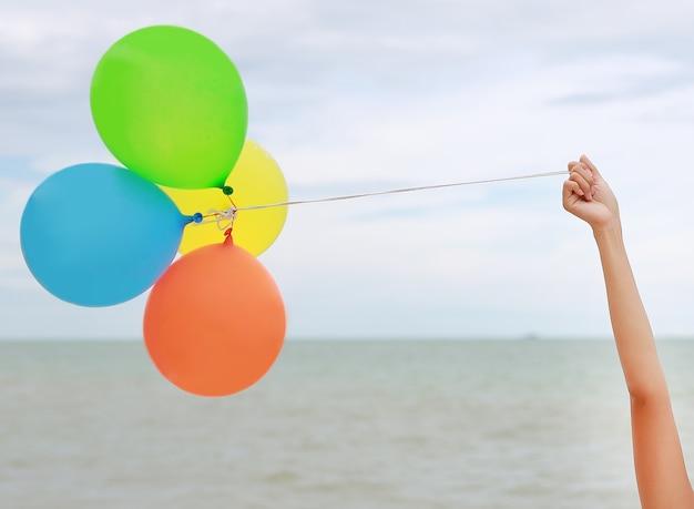 Mão de menina segurando balões coloridos na praia