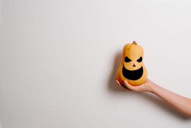 Mão de menina segurando uma abóbora de halloween
