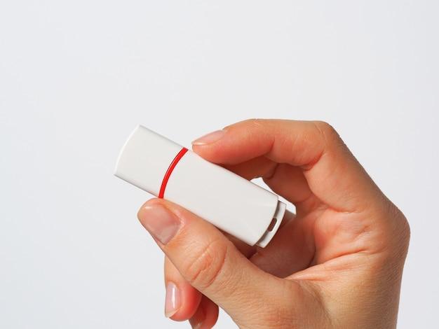 Mão de menina segurando uma unidade flash usb branca