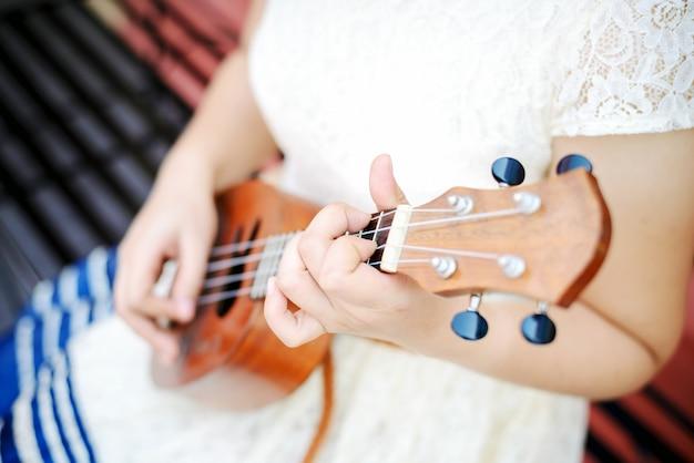 Mão de menina tocando ukulele