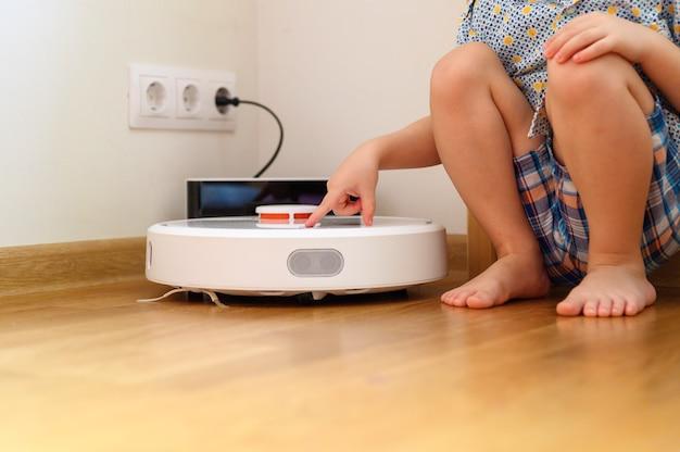 Mão de menino crianças pressiona o botão para ligar o aspirador de pó robô. limpeza doméstica
