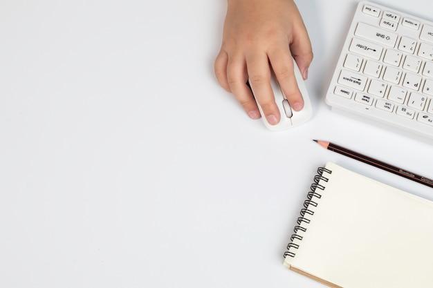 Mão de menino de vista superior com teclado e mouse