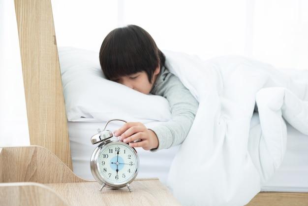 Mão de menino estendendo a mão para o despertador de manhã enquanto estava deitado na cama