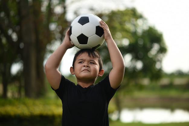 Mão de menino pequeno segurando futebol futebol