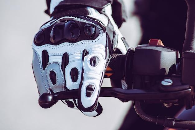 Mão de motociclista com luva protetora em ação andando na estrada - tonificada com um filtro instagram vintage retrô