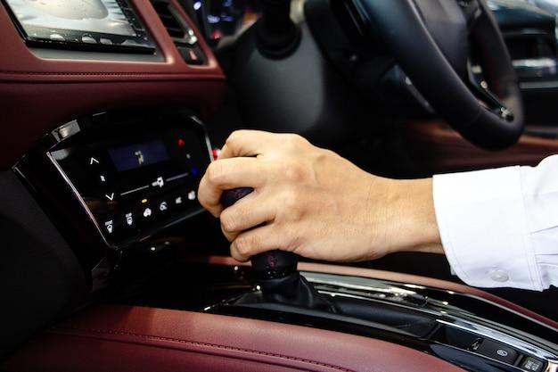 Mão de motorista de homem de negócios mudando a alavanca de câmbio com console vermelho.