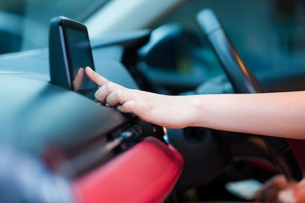 Mão de motorista, inserindo um endereço para o sistema de navegação ou música de rádio no carro