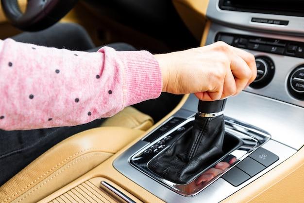 Mão de motorista mulher deslocando a alavanca de câmbio
