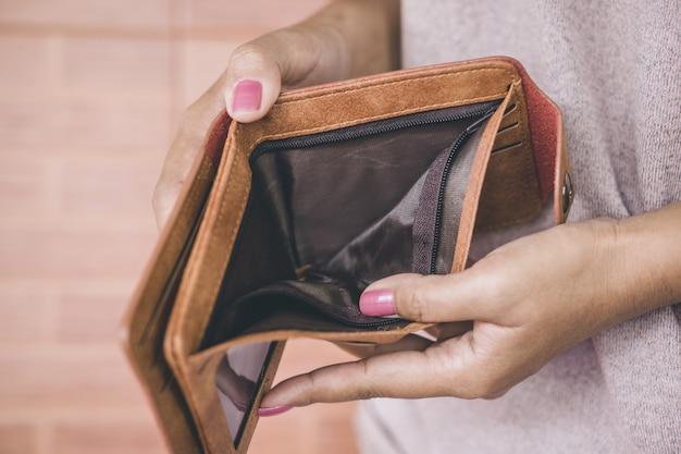 Mão de mulher abre a carteira vazia closeup