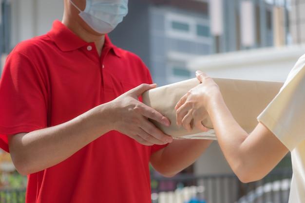 Mão de mulher aceitando uma entrega de caixas de entregador. compras online. quarentena. covid-19