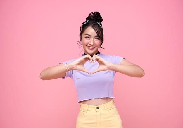 Mão de mulher adolescente asiática feliz mostrando mini gesto de coração sobre fundo rosa.