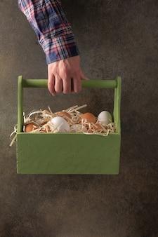 Mão de mulher agricultora segura uma caixa de madeira com ovos marrons e brancos em palha contra um fundo escuro.