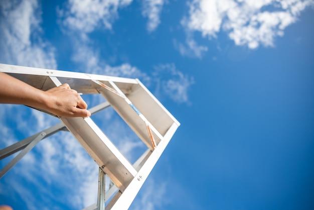 Mão de mulher, alcançando a escada vermelha, levando a um céu azul passo a passo