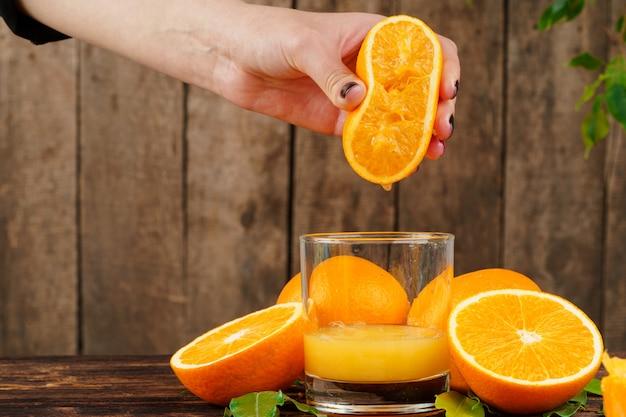 Mão de mulher aperta suco de laranja close-up