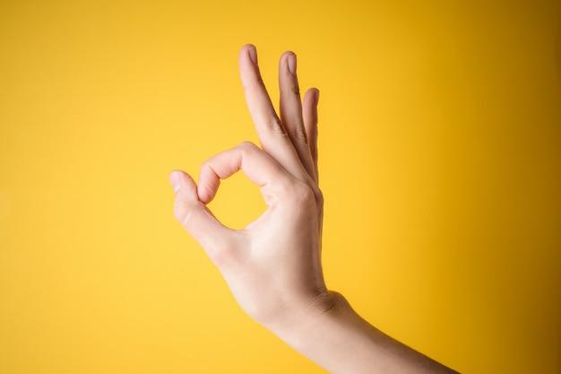 Mão de mulher apontando gesto bem