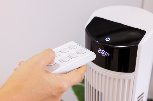 Mão de mulher asiática do close up pressionando um botão na máquina do purificador de ar em um quarto protect pm 25