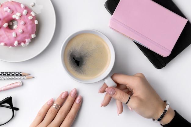 Mão de mulher bem cuidada, segurando a xícara de café branca