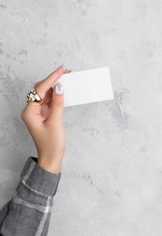 Mão de mulher bem cuidada, segurando o cartão na mesa de concreto cinza