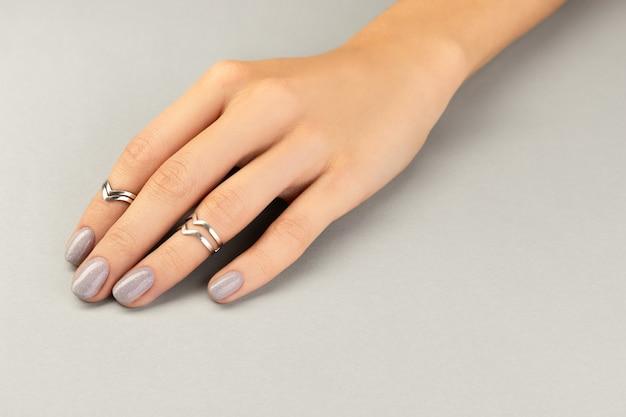 Mão de mulher bonita bem cuidada com design mínimo de unhas em cinza
